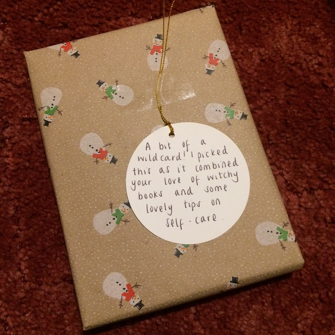Wrapped present with tag reading, A bit of a wildcard! I picked this as it combined your love of witchy books and some lovely tips on self care.