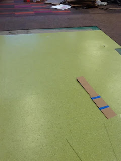 portion of floor with outer part carpeted and inner part with green subflooring