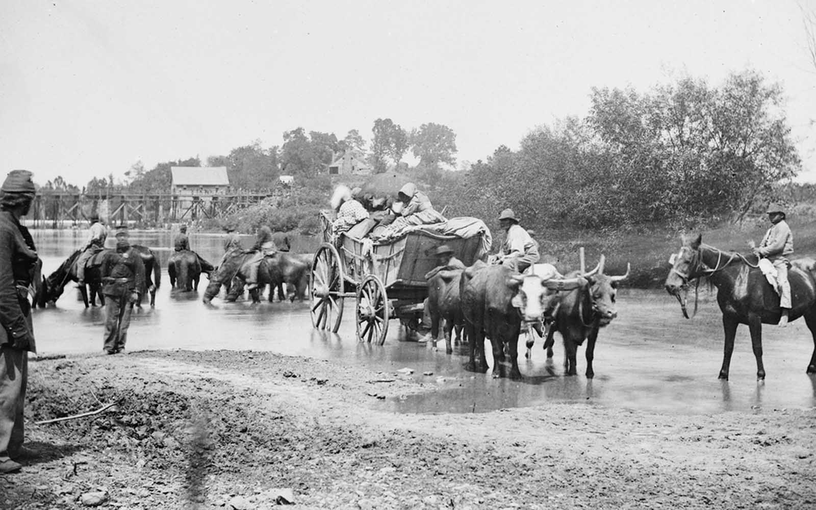 Fugitive African Americans are fording the Rappahannock River in Virginia, August 1862, during the Second Battle of Bull Run.