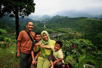 Berfoto bersama keluarga di sekitar gerbang masuk Obyek Wisata Guci, dengan latar belakang Gunung Slamet yang tertutup awan