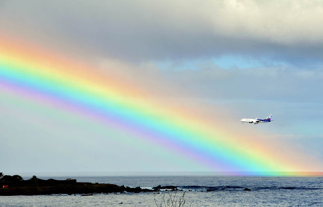 A plane is seen next to a rainbow on Ankaro Bay in Easter Island, off the Chilean coast in the Pacific Ocean.