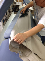 Khakis being folded after proper cleaning and pressing at A Cleaner World
