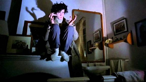 Fotograma en el cual Pedro conoce a José Sirgado, aparece en cuclillas sentado sobre un mueble agarrando un osos de peluche