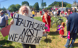 Michael Heinrich with a protest sign: Healthcare not wealthcare