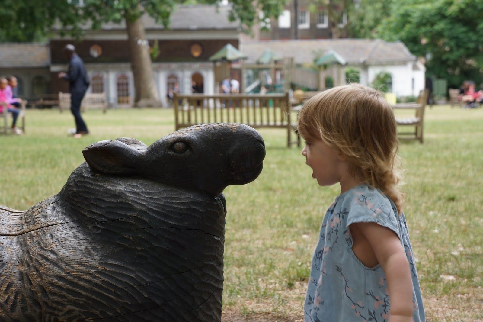 toddler and sheep statue looking at each other at coram's fields park