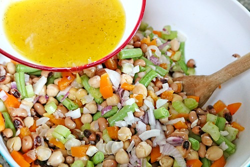 Tangy Chickpea Salad- Need to whip up a large side dish fast? It only takes minutes to put together this tasty and tangy chickpea salad! It's a great side for a barbecue! | bean salad, easy recipes for busy moms, vegetarian, homemade salad dressing, garbanzo beans