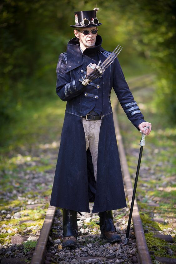 Man dressed as steampunk wolverine with wolverine glove claw, top hat, goggle, coat, sunglasses. Men's steampunk fashion and cosplay