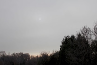 faint sun behind early December clouds