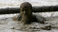 Bearded man in mud up to shoulders