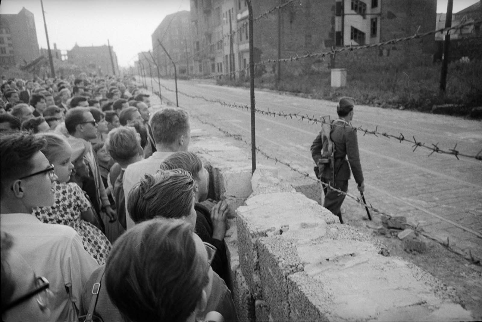 A crowd of West Berliners gathers at the newly erected Berlin Wall while an East German soldier patrols on the other side in August 1961