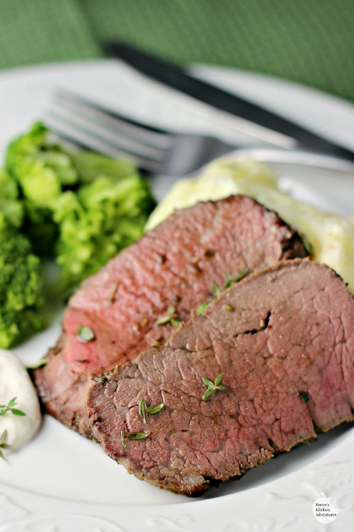 Garlic Herb Beef Tenderloin Roast with Creamy Horseradish Sauce slices on plate ready to eat