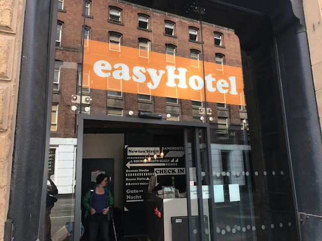 A glass door with easyHotel written above it and a view into a small reception area