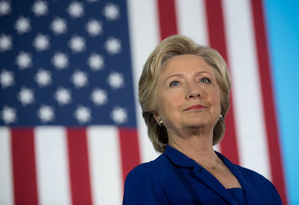 image of Hillary Clinton in a bright blue suit standing in front of a U.S. flag, looking very presidential