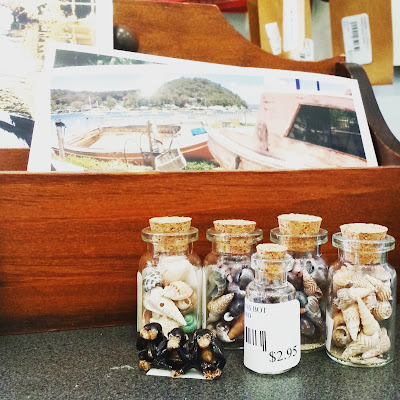 Selection of bottles containing miniature shells in front of a box displaying postcards.