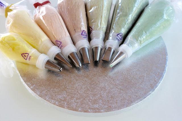 Buttercreme in verschiedenen Spritzbeuteln mit Adaptern und verschiedenen Tüllen