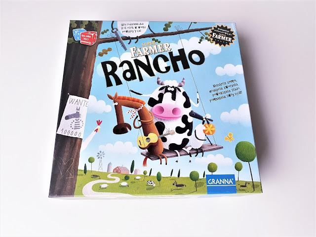 na zdjęciu karton od gry Superfarmer Rancho a na nim krowa, koń i owca bujają się na chuśtawce zawieszonej na drzewie
