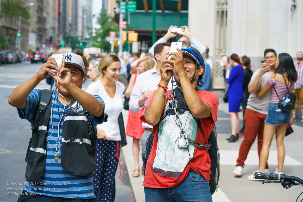 a photo of bike messengers in new york viewing the eclipse