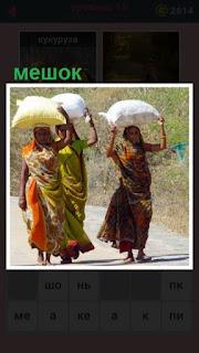 по дороге двигаются несколько женщин с мешками на головах