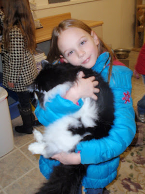 Young girl in blue coat holding black and white cat