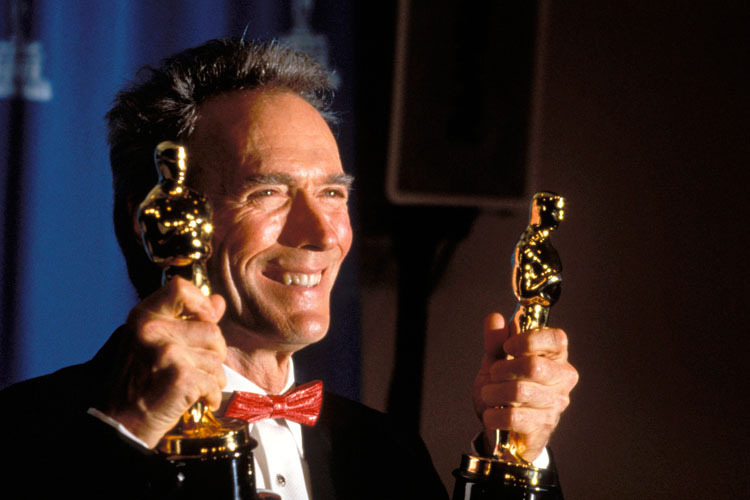Clint Eastwood holding Oscars Unforgiven 1992 movieloversreviews.filminspector.com