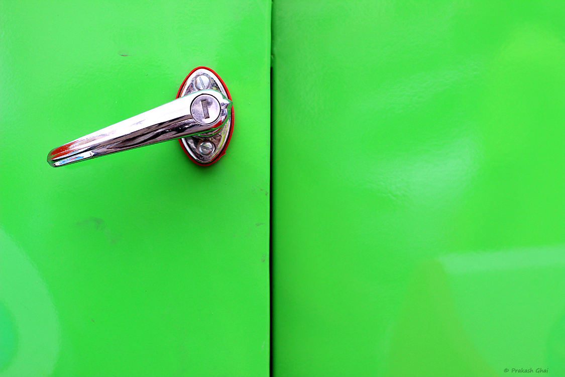 A minimalist photo of A green door with a metal handle