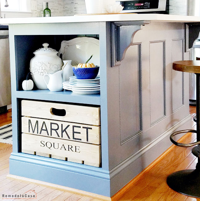 grey kitchen island with wooden crate on shelf