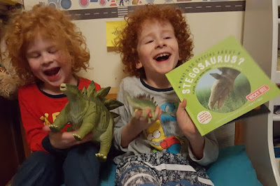 two boys holding stegosaurus book and plastic toy stegosaurus