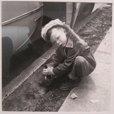 Young boy in coonskin cap, squatting beside a car, digging in the dirt, looking up at the photographer almost angrily
