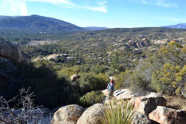 hikers balancing along a rock downward