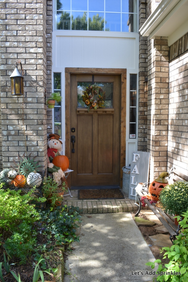 Planter filled with pumpkins, bench, scarecrowLantern on front porch.