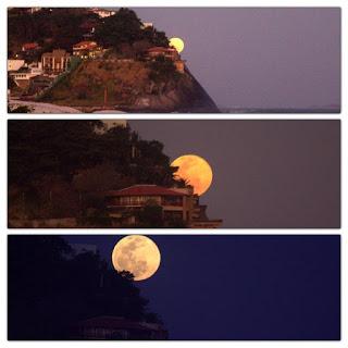 Foto tirada por Mariana Bittencourt. Composição em três linhas de uma sequência de fotos. De cima para baixo: Linha 1: À esquerda, a encosta de um morro com casas quase escondidas pela intensa vegetação. No perfil do morro, desponta parte da lua brilhante em um céu ao entardecer. À direita, no horizonte, o mar. Linha 2: À esquerda, foco em parte da lua, maior e dourada, aparecendo em um céu um pouco mais escuro, no perfil da encosta entre a intensa vegetação e um casarão. Linha 3: À esquerda, a lua prateada quase por inteira, parte da copa de uma árvore encobre uma pequena região da superfície inferior esquerda e o luar, ilumina a parte superior do casarão e o céu escuro.
