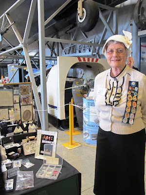A woman dressed in a 1940s outfit, standing in front of her stall at a miniatures convention.