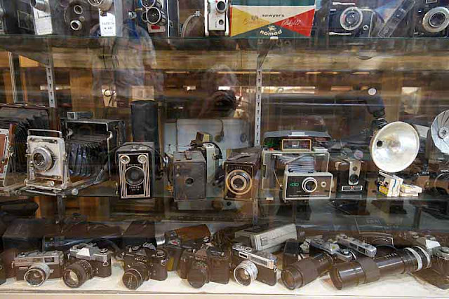 film cameras, lenses, flashes,glass case, relics