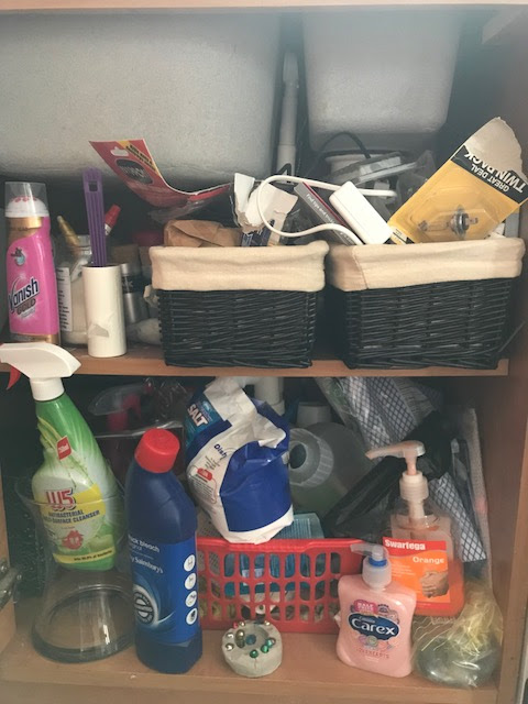 A very messy cupboard under a sink, showing cleaning items and vases
