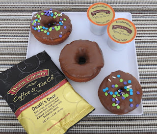 Chocolate frosted doughnuts on white plate with coffee