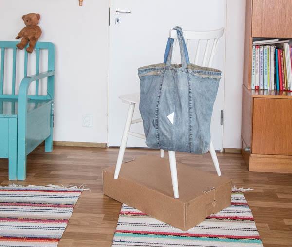 Näin kuvasin: Pahvilaatikon päällä tuoli, joka selkänojalla roikkuu kassi