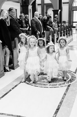 multiple flower girls walking down the aisle