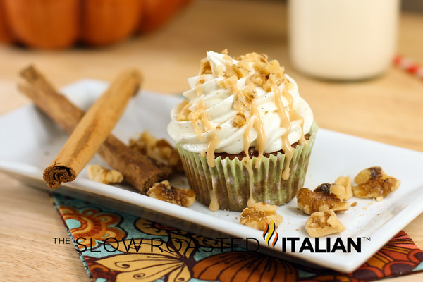 caramel apple cupcakes with cream cheese frosting swirled on top, sitting on white plate