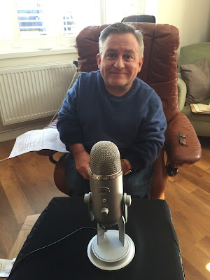 Simon Minty sitting behind a microphone