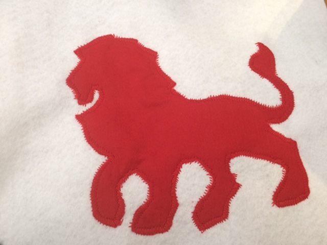 Red lion sewn on to white felt