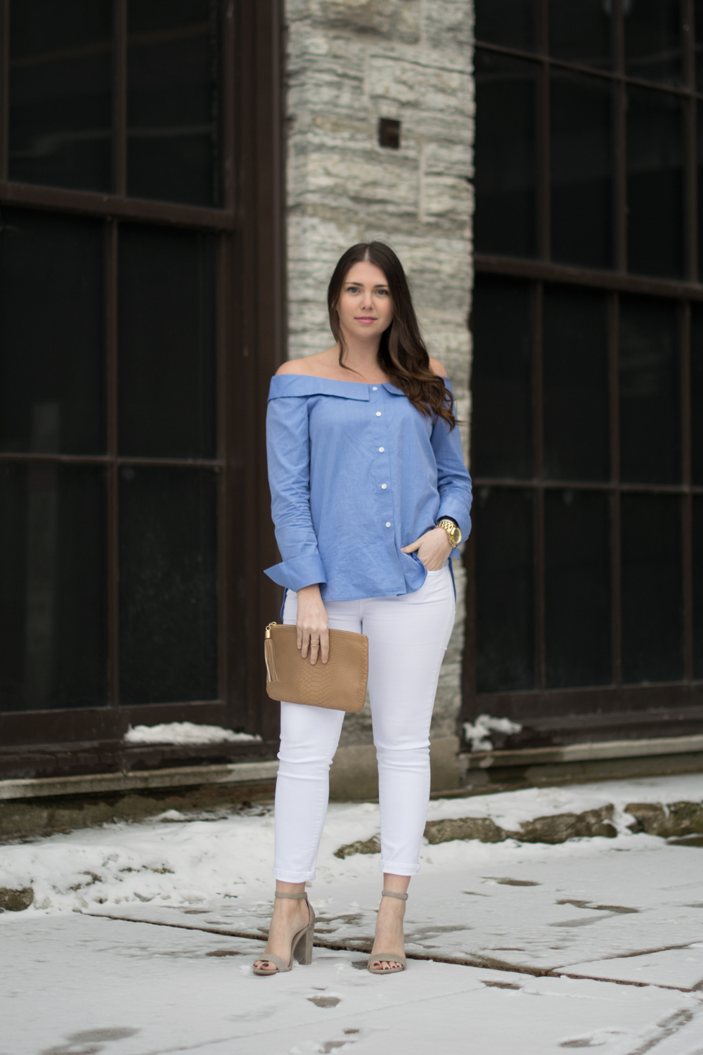 Young woman in blue off the shoulder top and white jeans.