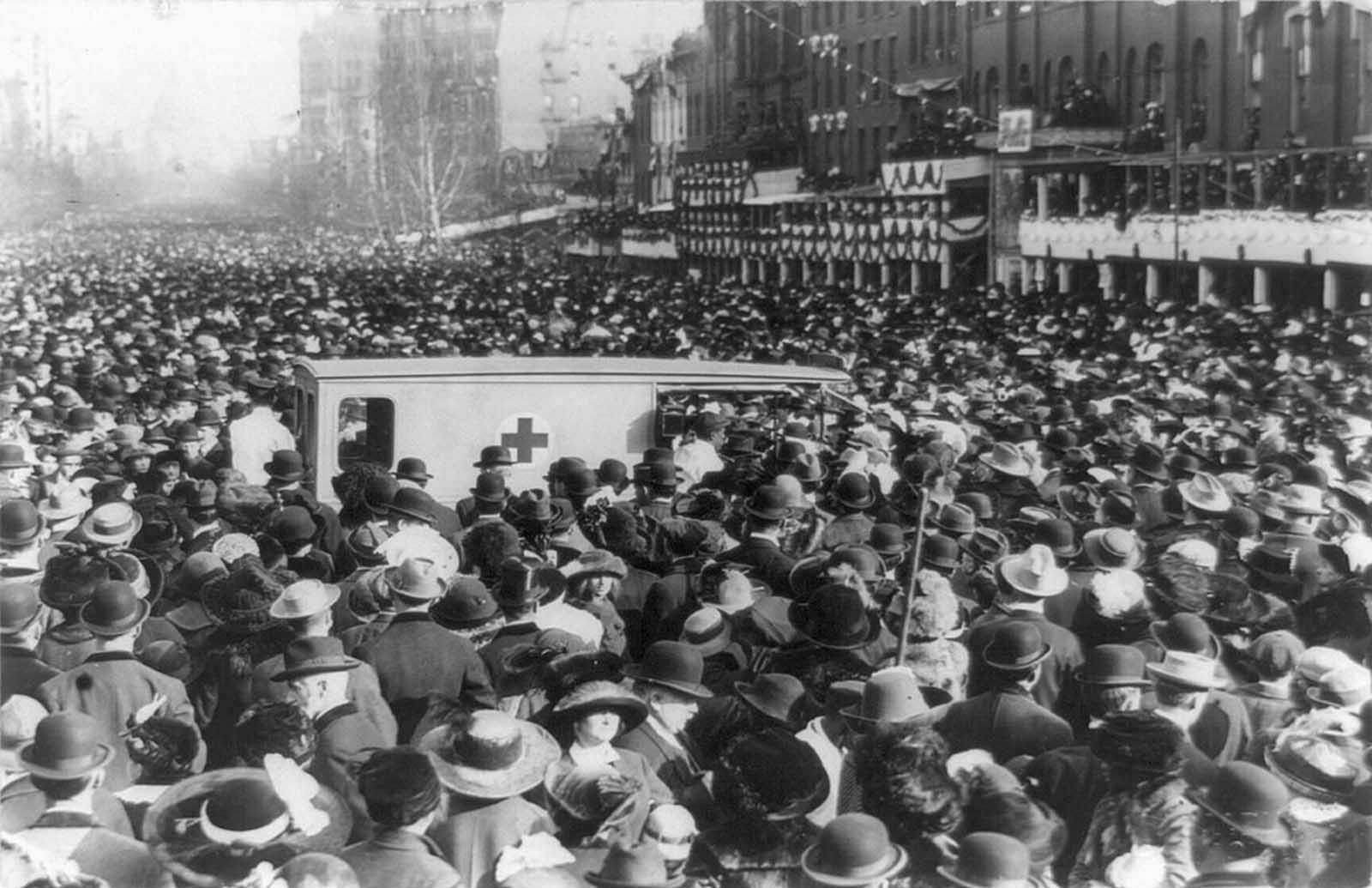 The crowd surrounds and slows a Red Cross ambulance during the Women's suffrage procession, on March 3, 1913. Dozens of marchers were injured during the march, shoved and tripped by spectators.