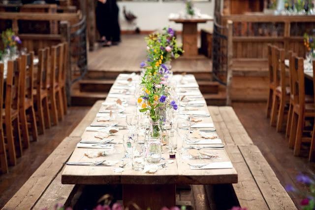 Long wooden bench dressed for a wedding reception
