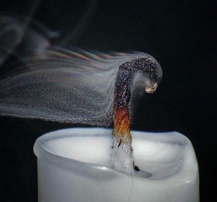 Una espelma després d'apagar-se la flama, a on es veu clarament que el fum està format per partícules molt petites.