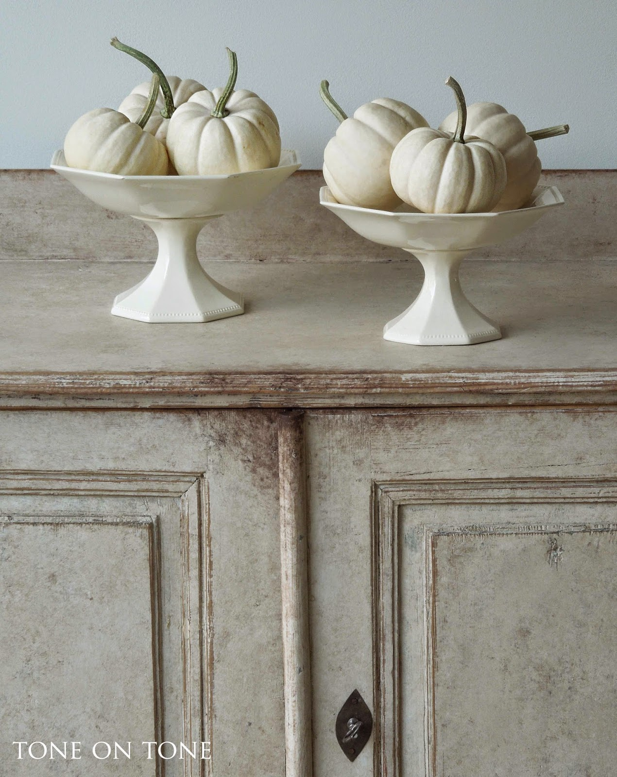 Baby boo white pumpkins in pedestals on antique Swedish cabinet