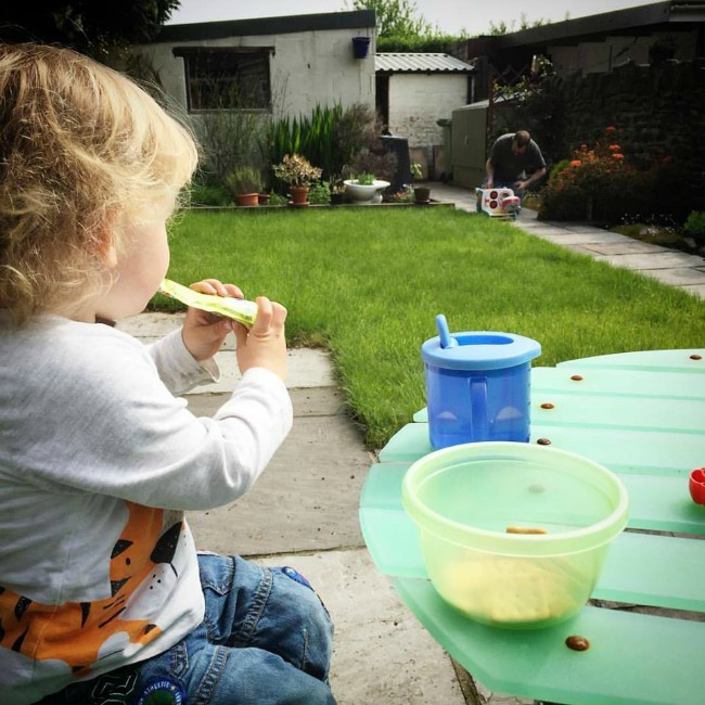 toddler-sat-at-table-in-garden-adult-in-background