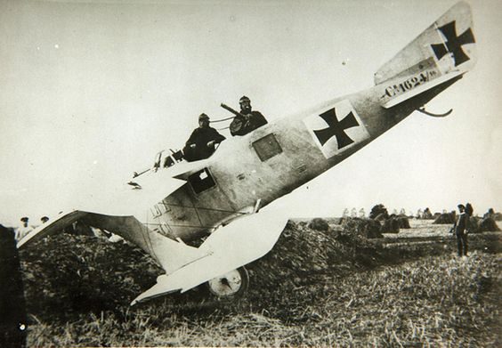 Photo of WWI airplane crash in a field. Two soldiers sit in a wrecked advanced German reconnaissance aircraft known as the Walfisch (Whale). Dogfights and other stories of pilots. marchmatron.com