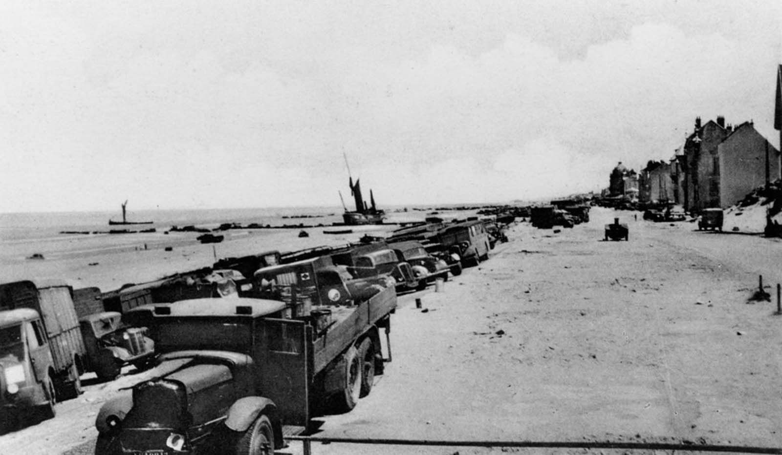 Abandoned trucks and equipment line the beach after the Allied evacuation.