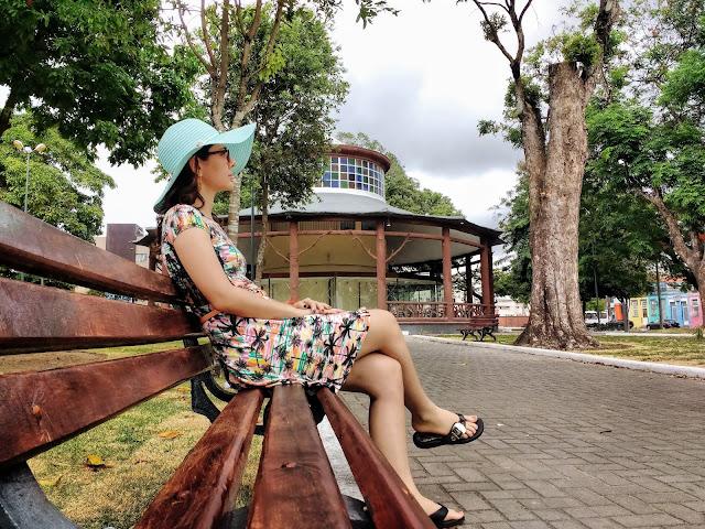 Liliam sentada em um banquinho da Praça Venâncio Neiva.
