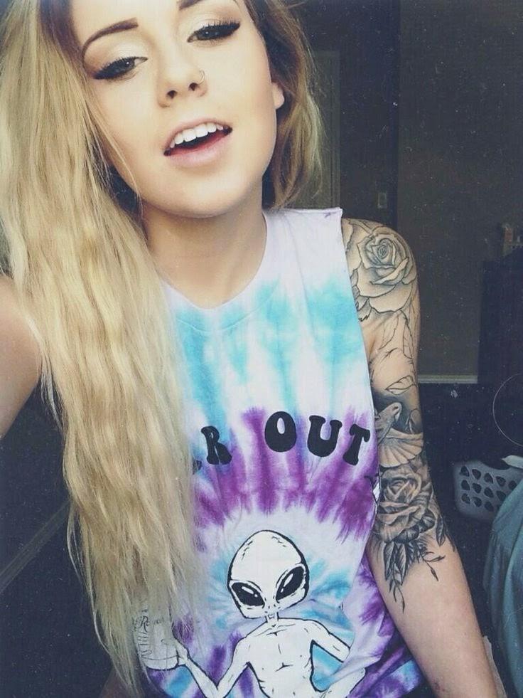chica jovencita rubia, lleva tatuajes en los brazos y sonríe mientras se fotografía
